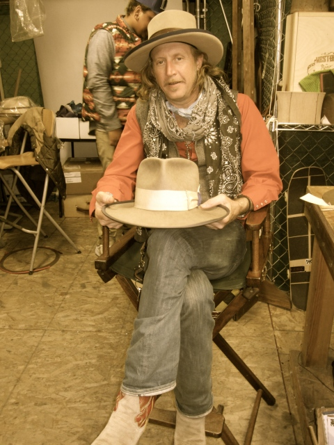 Gregory in his small studio holding the first cowboy hat he ever made.
