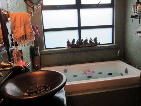 The bathroom with a tub of floating flowers to set the mood.