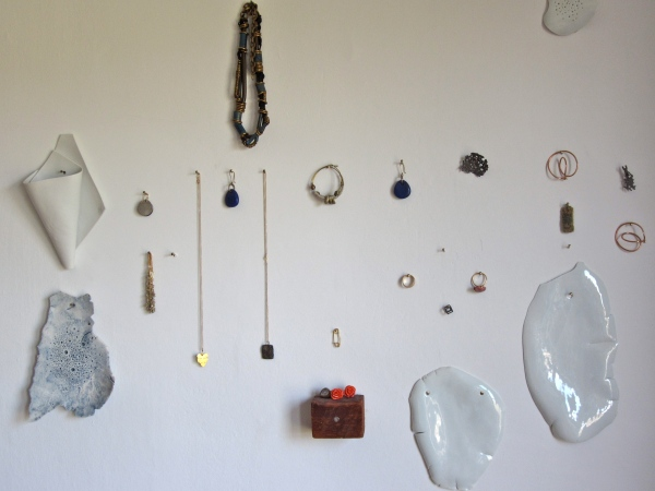 A collage of jewelry, pottery and special things hangs on her studio wall