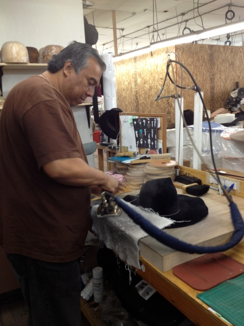 Her right hand man shaping a client's new hat
