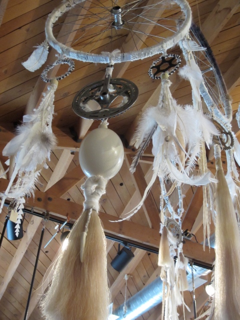 Dream catcher created from bicycle tires, feathers, horsehair, eggs, bike chain holders, leather and more