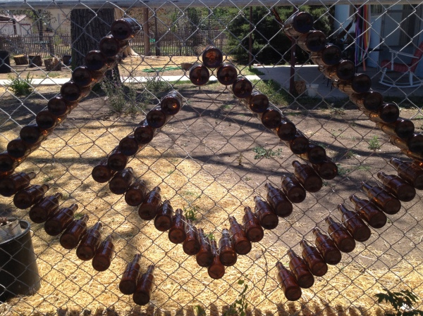 Creative up-cycling of bottles on her fence
