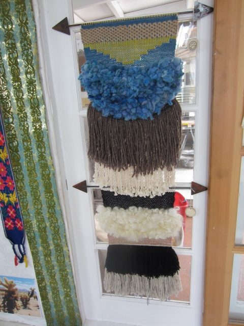 An All Roads weaving hanging in the studio